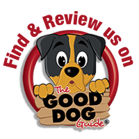 The Good Dog Guide logo. A brown and orange cartoon dog holding a wooden sign