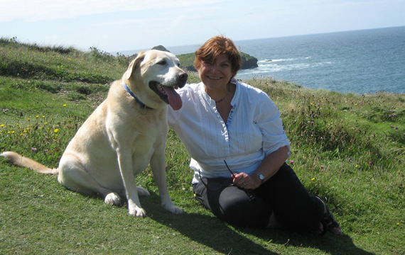 Marion and Louie the golden labrador, both sat on the grass, at the coast